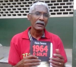 """Dutra mostra o livro de Flávio Tavares: """"É um livro muito interessante sobre o golpe de 64"""". Foto: Chico de Paula/Agência Biblioo"""
