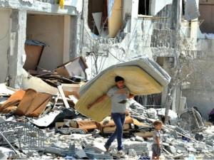 Crianças palestinas procuram por seus objetos, em casas destruídas por ataques israelenses na Faixa de Gaza, em agosto de 2014. Foto: SHAREEF SARHAN/ UN (07/08/2014)